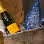 A bottle of fizz and a blue fish shaped plate resting in a rustic box