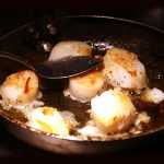 Fresh scallops frying in a pan