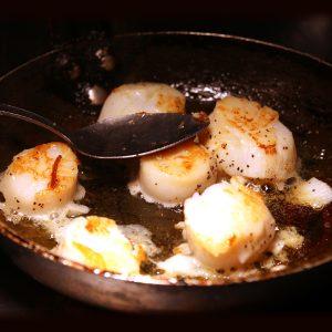 Fresh scallops frying in a pan
