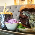 A tasty 16oz burger with melted cheese, served in a toasted bun with coleslaw and chips