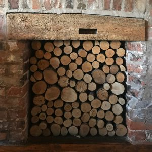 An old fireplace filled with wood logs to create a feature