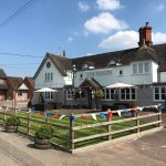 The Falcon at Hatton in the summer with blue skies and bunting along the fence