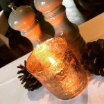 Warm glow from candle table decorations next to salt and pepper mills